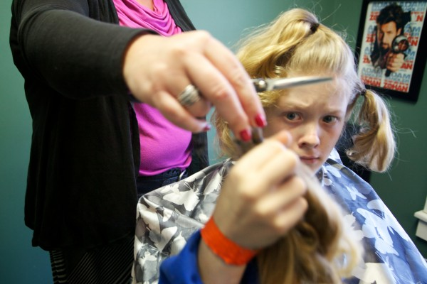 Josh Demers, 12, looks at his hair as he has it cut off for Locks of Love, an organization that makes wigs for cancer patients.