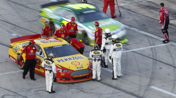 NASCAR officials penalize Joey Logano (22) for not being ready to join the grid in time before the race, placing him last for the start, during the NRA 500 on Saturday, April 13, 2013, at Texas Motor Speedway in Fort Worth, Texas.