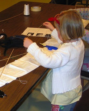A young girl works to construct a kite during a workshop at the Owls Head Transportation Museum.