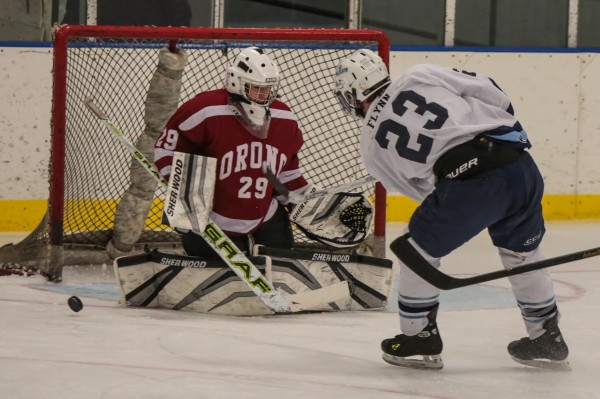 Orono goalie Michael Brown makes a save on a shot from Presque Isle's Adam Flynn during a recent game in Presque Isle. Orono and Old Town hope to field a cooperative hockey team next season.