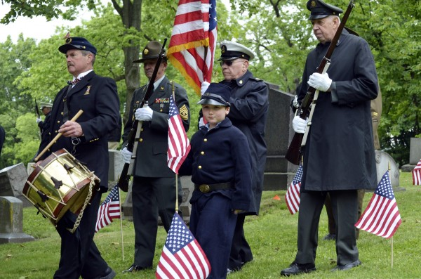 Jim Smith (left), 70, of Hempfield, Pa., leads members of the Grand Army of the Republic Post 88, Pittsburgh, and the Armbrust Veterans and Civil War Re-enactors, including Luke Prohaska (center) in a Civil War uniform, for a ceremony at the graveside of Peter Guibert, a Union Civil War drummer boy, in Pittsburgh, Pa., on Friday. Fifty years after the Battle of Gettysburg, the bloodiest of the Civil War, Guibert, a survivor of that fight, marched 200 miles from Pittsburgh to the site of the battle for a reunion attended by both Union and Confederate veterans. On Sunday, Smith, another veteran, started out on the same trek as part of the observation of Memorial Day. By a stroke of luck, Smith carried the same drum — a throaty field snare — played by his spiritual forebear, Guibert.