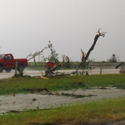 A pickup passes by tornado debris in the Westbound lane of Interstate-40, just east of El Reno, Okla., on Friday.  Violent thunderstorms spawned tornadoes that menaced Oklahoma City and its already hard-hit suburb of Moore.