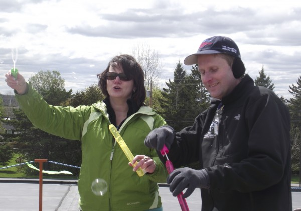 Jason Parent, right, director of advancement for The Aroostook Medical Center, and Lisa Miles, general manager for then Cumulus Broadcasting in Presque Isle, blow bubbles on top of the roof at The Aroostook Medical Center on Thursday, May 17, 2012, to try and attract the attention of passersby. The two began camping out on the TAMC roof in May 2012 as part of the inaugural Rally On The Roof fundraiser.