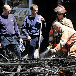 Lewiston firefighters douse a smoldering section of what was a four bay garage behind 116 Pierce St. Saturday.