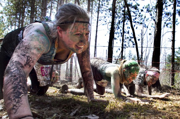 Keri DuFresne, left, and her Running Wild teammates crawl under trip lines in the &quotEnchanted Forest&quot obstacle during the Into The Mud Challenge, Sunday, April 28, 2013, in Gorham, Maine.