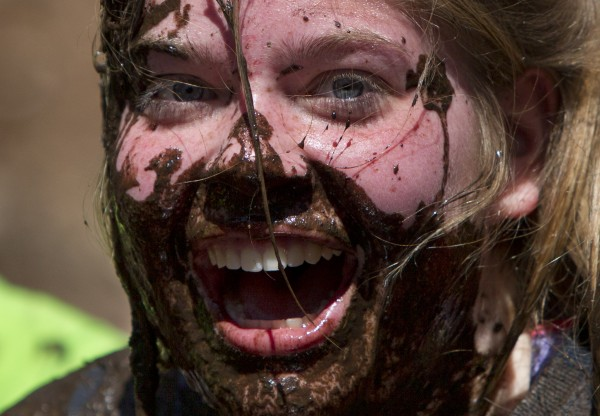 A woman reacts after falling up to her nose into a mud pit during the Into The Mud Challenge, Sunday, April 28, 2013, in Gorham, Maine.