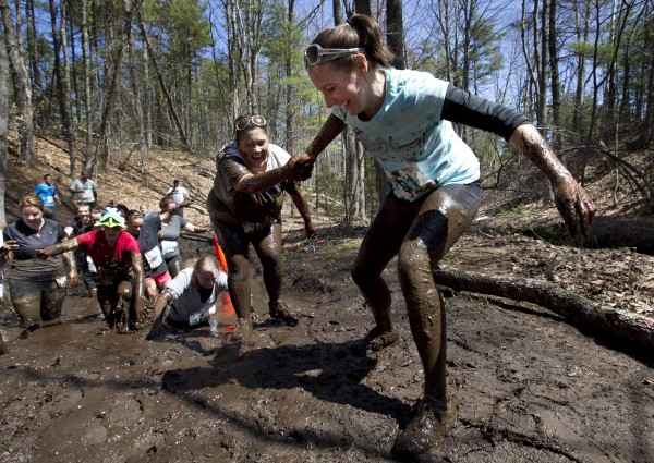 Racers help each other get through &quotGot Mud,&quot an obstacle in the Into The Mud Challenge, Sunday, April 28, 2013, in Gorham, Maine.