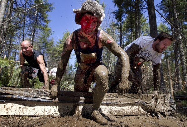 Racers climb out the &quotCamo Crawl&quot — an obstacle that resembles a child's sandbox, only filled with mud — during the Into The Mud Challenge, Sunday, April 28, 2013, in Gorham, Maine.