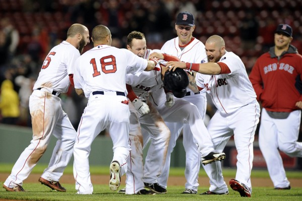 Boston's Stephen Drew (wearing helmet) is mobbed by his Red Sox teammates after hitting a game-winning double during the 11th inning against the Minnesota Twins Monday night at Fenway Park in Boston.
