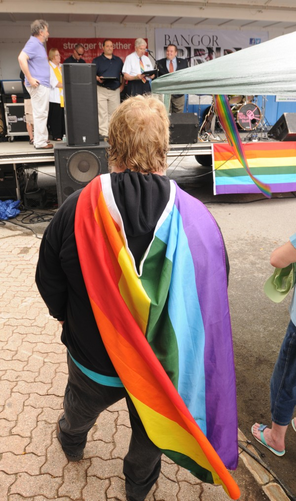 Adam Hansen of Bangor listen as local officials make remarks during the opening of the Bangor Pride Festival in West Market Square on Saturday.