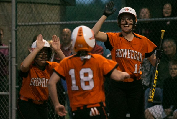 Skowhegan's Morgan Buker (right) and Taylor Johnson (left) congratulate Anne-Marie Provencal (center) after she scored a run in Saturday night's Eastern Maine Class A softball semifinal at Coffin Field in Brewer. The Indians won 5-2.