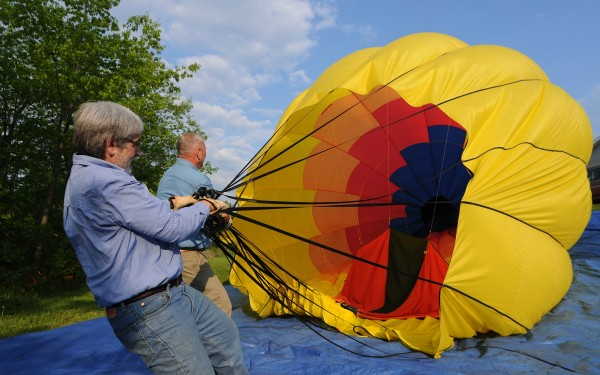 Balloonist Joe Hamilton, right, gets help from ground crew member Joe Stupak, left, as the pair breaks down Hamilton's balloon in the yard of a Dover Foxcroft resident after a flight during the Piscataquis Heritage Hot Air Balloon Festival in Dover-Foxcroft on Friday.