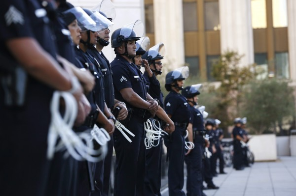 Police officers stand guard outside the police headquarters during a rally organized by the Act Now to Stop War and End Racism (ANSWER) coalition to protest the acquittal of George Zimmerman for the shooting death of Florida teenager Trayvon Martin, in Los Angeles, California July 16, 2013.