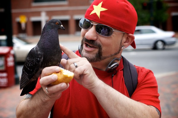 Starr Sarabia strokes a pigeon's feathers in Portland's Congress Square while feeding it a doughnut.