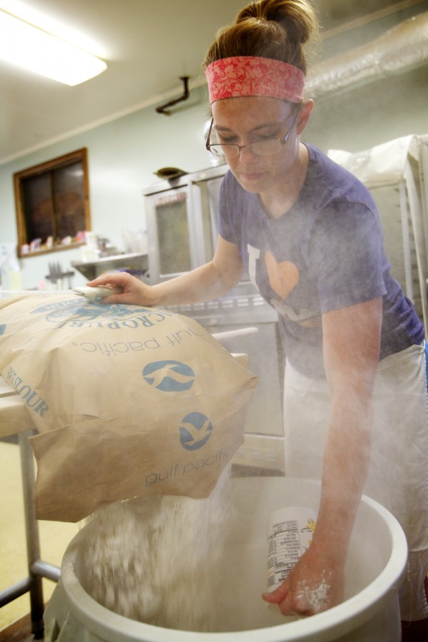 Melanie Roy empties a bag of flour at Scratch Baking Co. in South Portland on Wednesday. Given the amount of flour slung in the course of making bread, fans are a bad idea, even in the hot weather.
