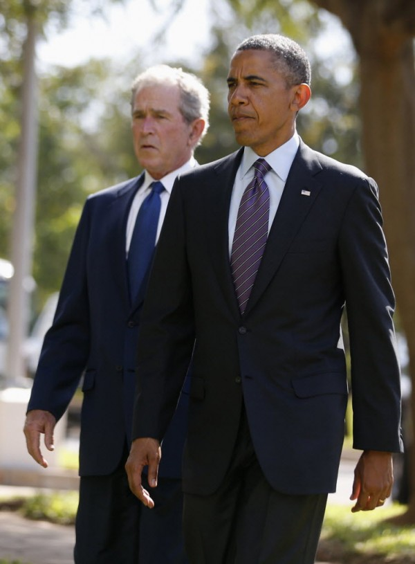 U.S. President Barack Obama (R) and former President George W. Bush attend a memorial for the victims of the 1998 U.S. Embassy bombing in Dar es Salaam, July 2, 2013.