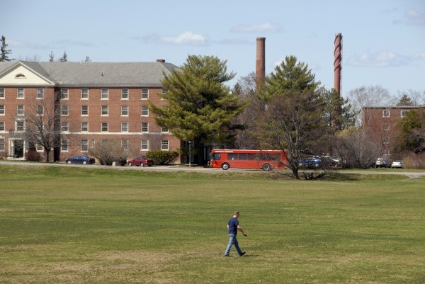 A student walks across Lengyel Recreation Field as a BAT bus travels along Munson Road past Chadbourne Hall on the University of Maine campus. The UMaine Steam Plant chimneys rise in the distance. Photo taken on Thursday, April 25, 2013.