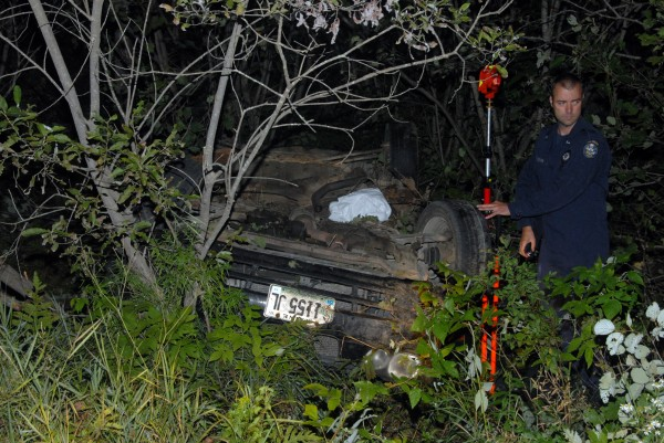State police Trooper Larry Anderson takes measurements from the sedan that veered from Aroostook Road and crashed in Molunkus Township on Monday, Aug. 26, 2013.