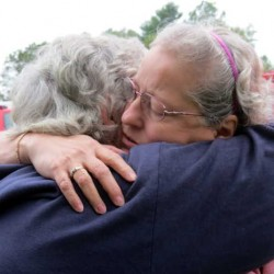Homeowner Laura Freeman, right, is comforted by her neighbor and friend Judy Hawley, as firefighters battle flames erupted in Freeman's garage and spread to the house early Thursday evening at 8 Summerland St. in Paris.