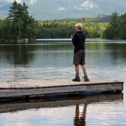 Will Greene, 16, of Bar Harbor, stands on the Katahdin Lake Wilderness Camps dock on the south shore of Katahdin Lake on Aug. 10, 2013, in Baxter State Park, while participating in the 2013 Maine Youth Wilderness Leadership Program organized by Friends of Baxter State Park.
