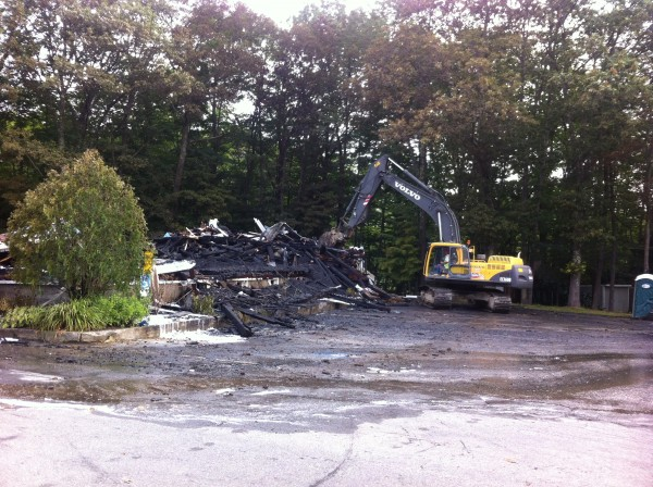 An excavator demolishes the remaining charred walls of the Westcustogo Grange Hall in North Yarmouth on Friday morning.