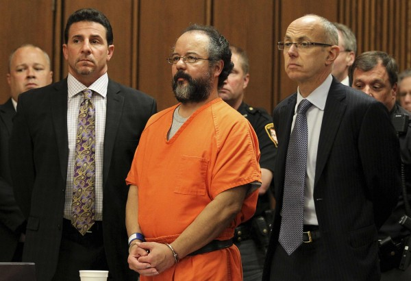 Ariel Castro, 53, stands between attorneys Craig Weintraub, left, and Jaye Schlachet as his sentence is read to him by judge Michael J. Russo in the courtroom in Cleveland, Ohio August 1, 2013. An Ohio judge on Thursday sentenced Cleveland kidnapper Ariel Castro to life in prison for abducting, raping and holding captive three women for as long as 11 years, and murder for forcing one of the women to abort her pregnancy.