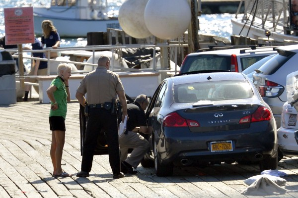 From left, vehicle operator Cheryl Torgerson, Knox County Sheriff's Sgt. John Palmer and Lt. Kirk Guerette look over the car that Torgerson was driving after she allegedly lost control, struck several cars and a family, killing a 9-year-old boy Sunday afternoon at the Monhegan Boat Landing in Port Clyde.