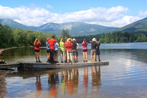 The 2013 Maine Youth Wilderness Leadership Program group, 10 Maine high school students led by Chewonki trip leaders Matt Stern and Annika Alexander-Ozinskas, stand on a dock at the south shore of Katahdin Lake on Aug. 10, 2013, their eighth day backpacking in Baxter State Park.