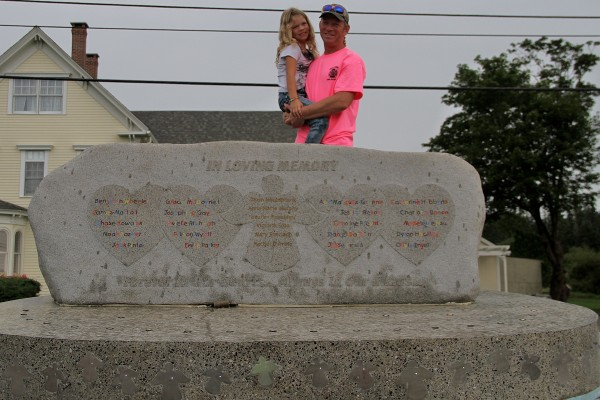 Richard Gray and his daughter Jayden stand behind the Rock of Angels memorial that will be sent to Newtown, Conn., in memorial of the teachers and students killed during the Sandy Hook Elementary School shooting.