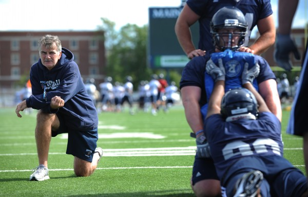 UMaine head coach Jack Cosgrove watches as the UMaine defense run drills on Morse Field during the first practice of the season Monday.