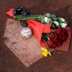 A written note can be seen with flowers and a baseball on the Essendon Baseball Club's home plate in Melbourne, Australia, as a tribute to Chris Lane on Wednesday. Lane, 23, who played baseball at the Melbourne club, was found dead of a gunshot wound on Friday, according to police in Duncan, Okla.