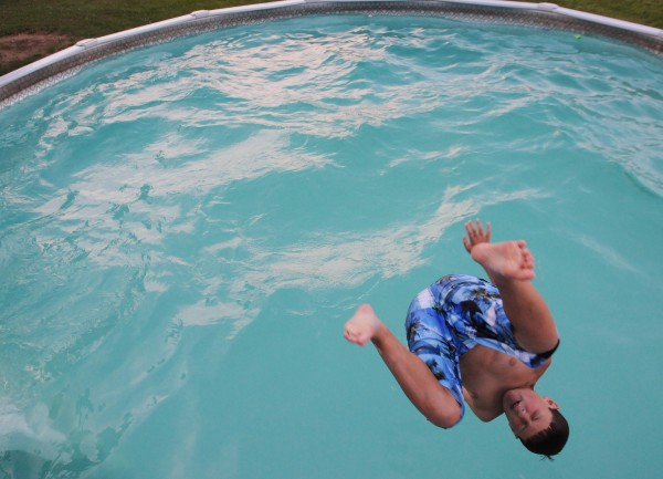NicolasJohnson does a back flip into his family's backyard pool during a pool party.