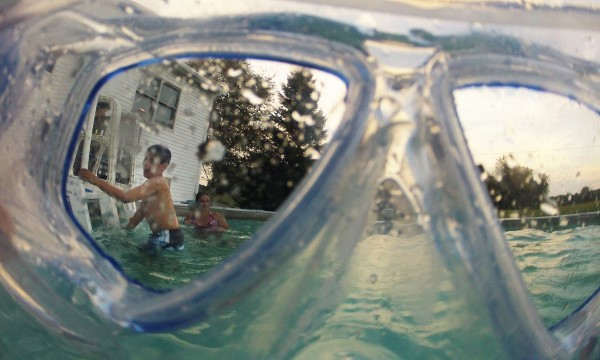 Nicolas Johnson climbs out of his family's backyard pool, as seen through a set of swimming goggles recently.