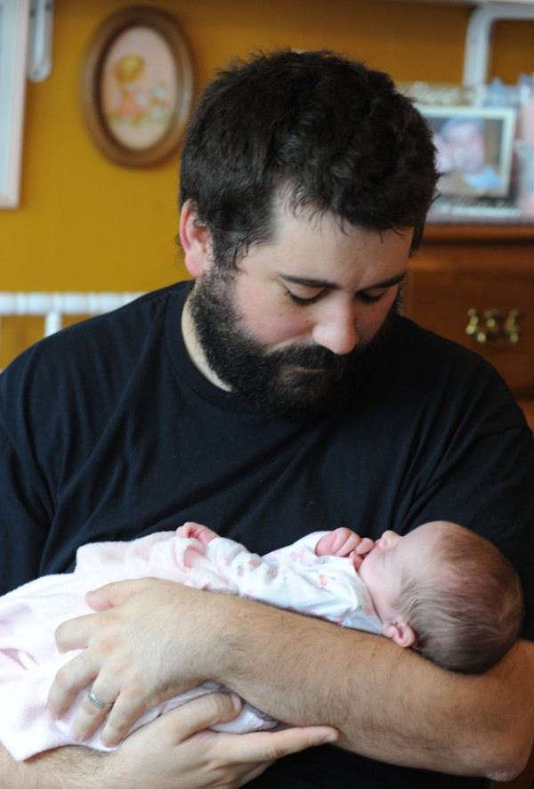 Matt Nichols holds his two-week-old baby, Ruby Ann, in his Bangor home.