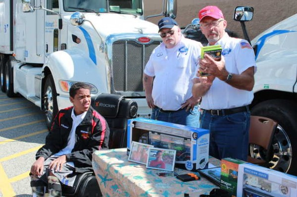 Devante Dupree, left, of Mexico sits in his new gaming chair Friday afternoon at Walmart in Mexico while Wal-Mart truck driver Fred Thompson, right, explains the games Dupree received. Wal-Mart Heart, a group of truck drivers who help raise money for children and adults with chronic medical conditions or special needs, hosted the event for Dupree, 13, who was born with cerebral palsy.