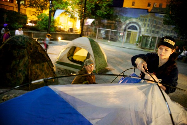 Occupiers Kara Oster (right) and Jarody (who goes by one name) set sup a tent in Portland's Congress Square Park Friday night. Protesters left the park around 11 p.m. after Police Chief Michael Sauschuck asked them to go.