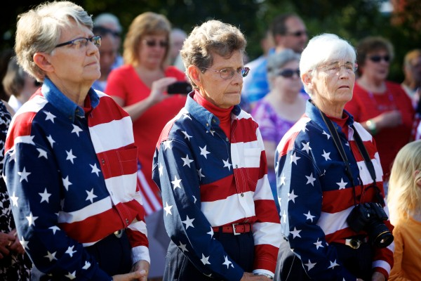 The Freeport Flag Ladies (from left) Elaine Greene, Carmen Footer and JoAnne Miller listen at a ceremony Wednesday morning marking the anniversary of Sept. 11, 2001, in Freeport.