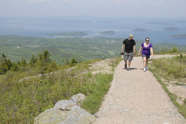 Taking advantage of the balmy temperatures, two tourists walk along the path that encircles the summit of Cadillac Mountain in Acadia National Park Saturday, June 1, 2012. Bar Harbor and the Porcupine Islands spread beyond the tourists.