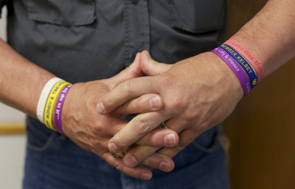 Arthur Jette is Womancare's community relations coordinator. Jette wears bracelets with names of several victims of domestic violence. Womancare is an organization that works to end domestic violence.