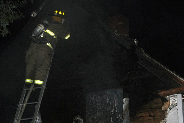 Lowell Fire Department firefighter John Herlihy peers into an attic space at 766 Dodlin Road in Enfield on Monday, Sept. 2, 2013.