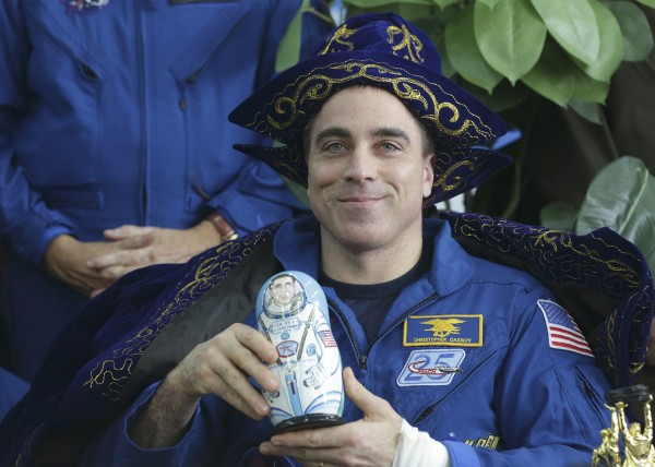 NASA astronaut Chris Cassidy holds up a traditional nesting doll of himself while wearing traditional dress during a press conference at the airport in Karaganda, Kazakhstan, Sept. 11, 2013.