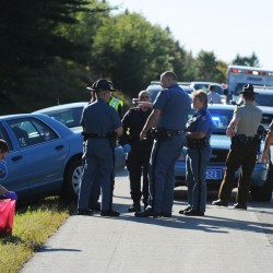 Members of law enforcement and rescue personnel discuss the high speed chase and crash of a pickup truck driven by Jason Brown along Interstate 95 at mile 170 in Carmel. Police put out three sets of spike mats before finally getting Brown off the road in Carmel.