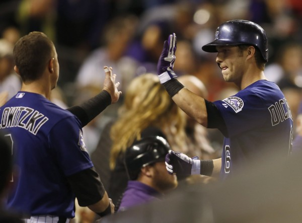 Colorado's Corey Dickerson (right) gets a high five from Troy Tulowitzki (left) after hitting a home run during the fourth inning against the Boston Red Sox at Coors Field in Denver Tuesday night. The Rockies won 8-3.