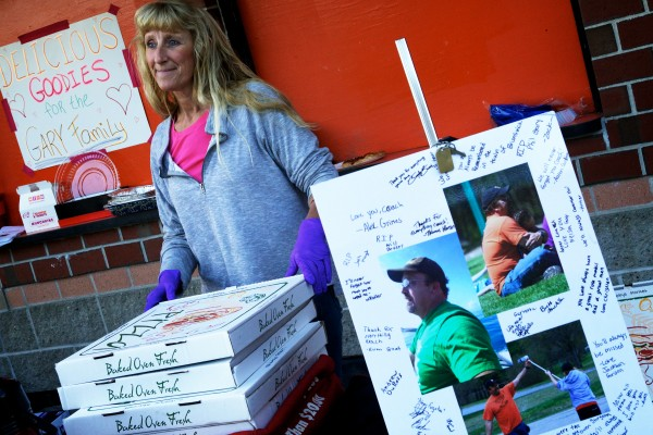 Jo-Ellyn Sturgeon sells pizza and goodies at a football game in Brunswick Thursday, raising money for the Gary family. Football coach and Boy Scout leader Phil Gary, 45, died unexpectedly on Tuesday leaving eight children and his wife Gail.