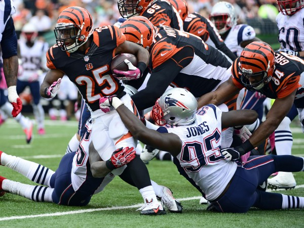 Cincinnati Bengals running back Giovani Bernard (25) gets tackled by New England Patriots cornerback Kyle Arrington (25) in the first half of the game at Paul Brown Stadium.