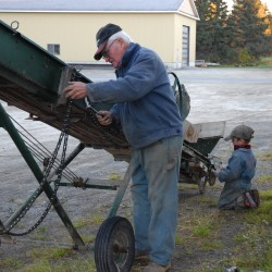 Farmer Raoul Caron gets some help from great-grandson Ethan making some repairs to a piece of potato harvesting equipment. Four generations of Carons were on the family farm during this year's harvest.