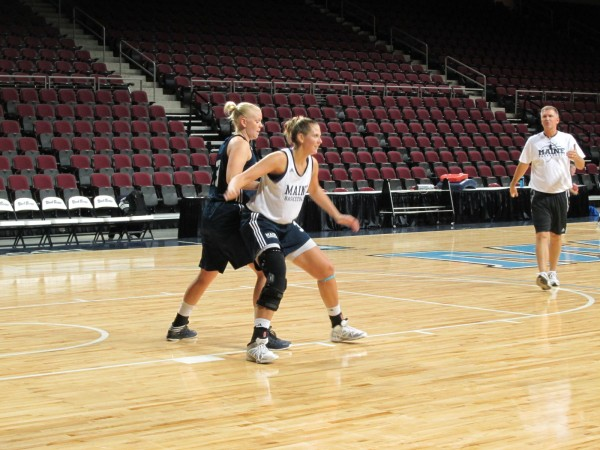 Ali Nalivaika (white jersey) of the University of Maine posts up against teammate Mikaela Gustafsson under the watchful eye of associate head coach Todd Steelman during an Oct. 22 practice at the Cross Insurance Center in Bangor. Nalivaika has returned after missing two seasons due to three knee surgeries.