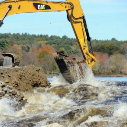Sargent Corporation uses a large excavator to start removing the 16,000 cubic yards of rock during the dam breaching on Oct. 10.