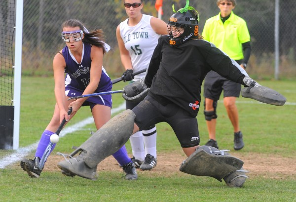 Old Town goalkeeper Erica Ogden (right) kicks the ball away from Waterville's Amber Hill during first-half action from Wednesday's Eastern Maine Class B quarterfinal field hockey game at Old Town. Ogden made 17 saves in the Coyotes' 2-1 win.