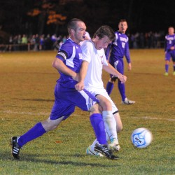 Hampden Academy's Jake Maltz (left) and Bangor High School's Sam Huston converge on the ball during their game in Bangor Tuesday evening. Hampden won 2-1 in overtime.
